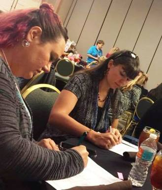 Maria & Amy fill out paperwork for their new state positions